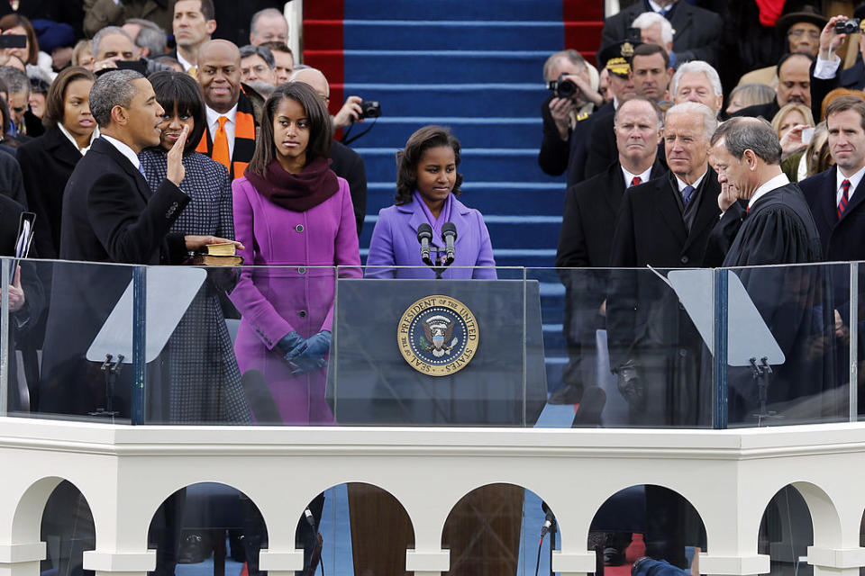 Barack Obama takes the presidential oath of office in 2009 with his family and Joe Biden standing next to him.