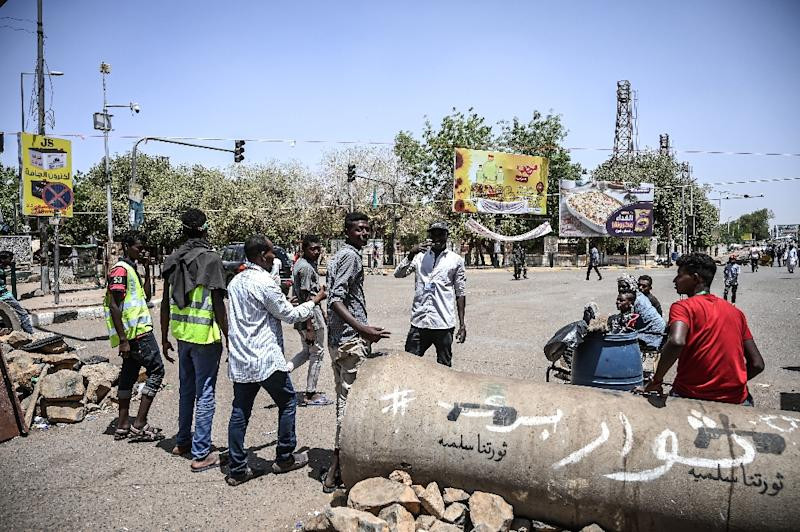 Sudanese protesters erect their own road block to search fellow demonstrators outside the army complex in the capital Khartoum on Sunday (AFP Photo/OZAN KOSE)