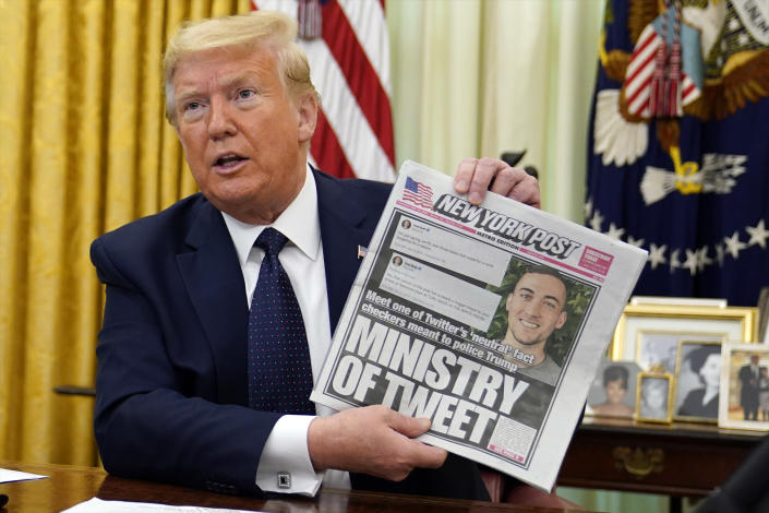President Donald Trump holds up a copy of the New York Post as he speaks before signing an executive order aimed at curbing protections for social media giants, in the Oval Office of the White House, Thursday, May 28, 2020, in Washington. (AP Photo/Evan Vucci)