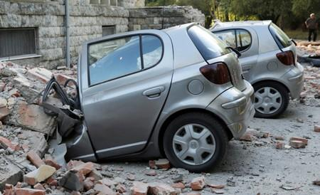 Destroyed cars stand next to a damaged building after an earthquake in Tirana