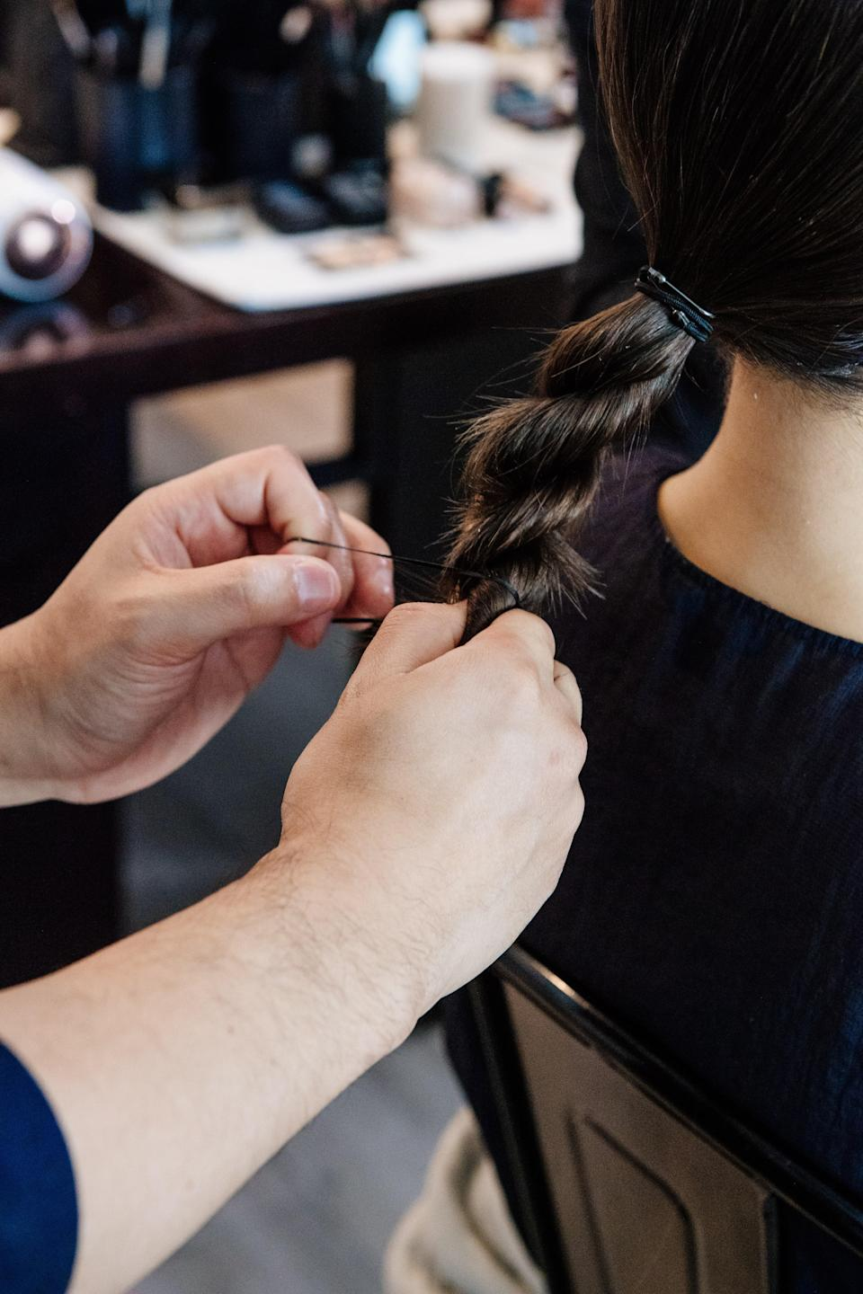 """Hairstylist Derek Yuen twisting Han's lengths into a super smooth chignon with help from <a href=""""https://us.phyto.com/phytodefrisant-anti-frizz-touch-up-care.html"""" rel=""""nofollow noopener"""" target=""""_blank"""" data-ylk=""""slk:Phyto's Phytodefrisant Anti-Frizz Touch-Up Care"""" class=""""link rapid-noclick-resp"""">Phyto's Phytodefrisant Anti-Frizz Touch-Up Care</a>."""