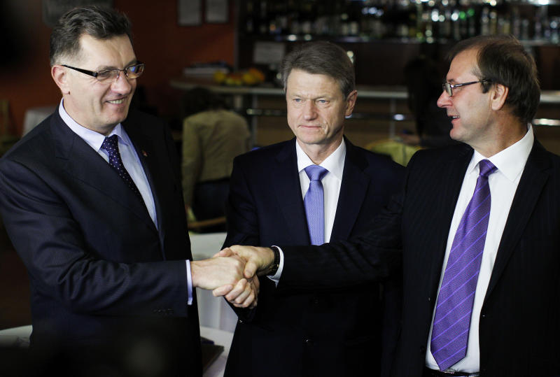 Social Democrat party leader Algirdas Butkevicius, left, Order and Justice party leader Rolandas Paksas,center, and Viktor Uspaskich, leader of the  Labor Party shake hands after the formal start of a coalition in Vilnius, Lithuania early Monday Oct. 29, 2012. (AP Photo/Mindaugas Kulbis)