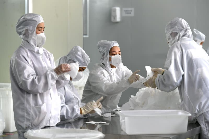 FILE PHOTO: Employees work on a production line manufacturing face masks at a factory, as the country is hit by an outbreak of the novel coronavirus, in Fuzhou