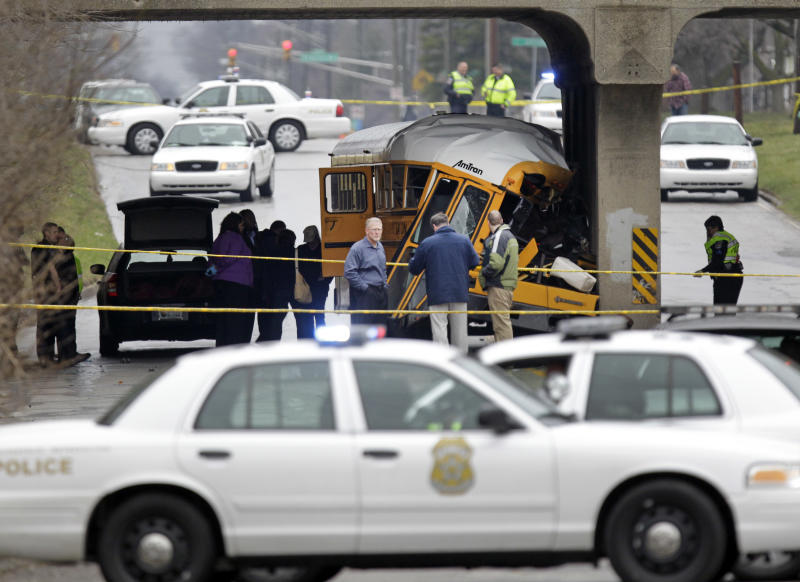 Investigators work the scene of a fatal bus crash on the southeast side of Indianapolis, Monday, March 12, 2012. The driver and one student were killed and two others critically injured. (AP Photo/Michael Conroy)