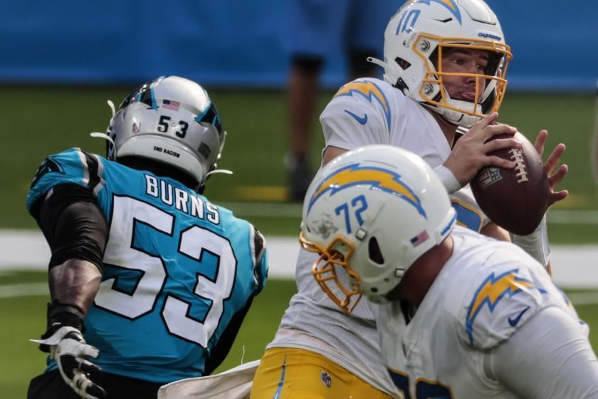 Inglewood, CA, Sunday, September 27, 2020 -Los Angeles Chargers quarterback Justin Herbert (10) delivers a pass under pressure against the Carolina Panthers at SoFi Stadium. (Robert Gauthier/ Los Angeles Times)