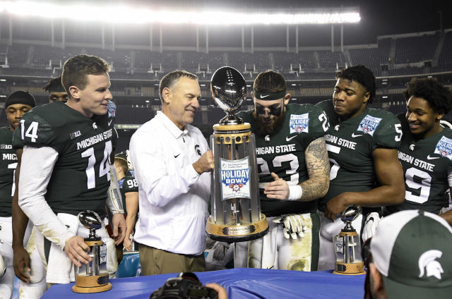 Michigan State head coach Mark Dantonio, center-left, holds up the Holiday Bowl trophy after beating Washington State 42-17. (AP Photo/Denis Poroy)