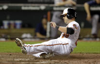 Baltimore Orioles' Steve Pearce slides across home plate for a run on a wild pitch by Boston Red Sox relief pitcher Matt Barnes in the seventh inning of a baseball game, Tuesday, June 9, 2015, in Baltimore. (AP Photo/Patrick Semansky)
