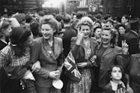<p>A group of overjoyed Londoners hold up peace signs while celebrating in the streets.</p>