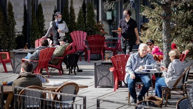 People lounge about at an outdoor patio  on a warm, sunny day in Ottawa during the COVID-19 pandemicin March. Dr. Doug Manuel says if the city's key COVID-19 indicators continue to decline, Ottawa could have a relatively similar summer to last year. (Brian Morris/CBC - image credit)
