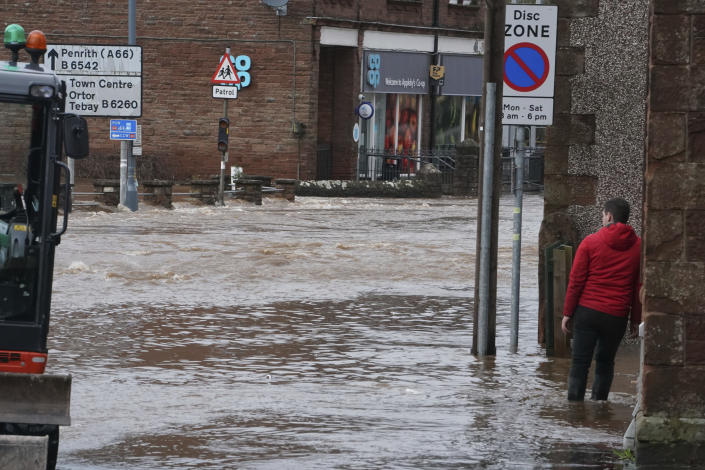 A man stands on flooded street, in Appleby-in-Westmorland, Cumbria, England, Sunday Feb. 9, 2020. Trains, flights and ferries have been cancelled and weather warnings issued across the United Kingdom as a storm with hurricane-force winds up to 80 mph (129 kph) batters the region. (Owen Humphreys/PA via AP)