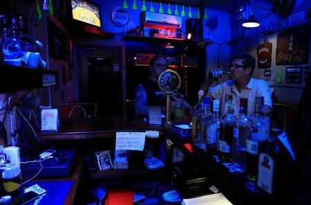 American James John Goodman (R), 51, drinks with his colleague inside a bar in Subic, north of Manila, Philippines November 10, 2017. Picture taken November 10, 2017. REUTERS/Romeo Ranoco