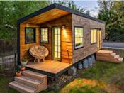 """<p>This 196-square-foot house near Boise, Idaho, is home to Macy Miller, her partner James, their daughter Hazel, and their Great Dane, Denver. A 27-year-old architect, Macy designed the home from scratch and built it on a 24-foot flatbed with help from friends and family. Clad in siding made of recycled pallet wood, the minimalist home is flooded with light and feels spacious despite its size. Hidden storage under the bed, above the pantry, and behind the fridge are contrasted with open shelving in the kitchen to make the space feel bigger. In total, Macy spent about $11,000 on her tiny house and is now able to live rent- and mortgage-free.</p><p><strong><a class=""""link rapid-noclick-resp"""" href=""""http://minimotives.com/pro-photos/"""" rel=""""nofollow noopener"""" target=""""_blank"""" data-ylk=""""slk:SEE INSIDE"""">SEE INSIDE</a></strong></p>"""