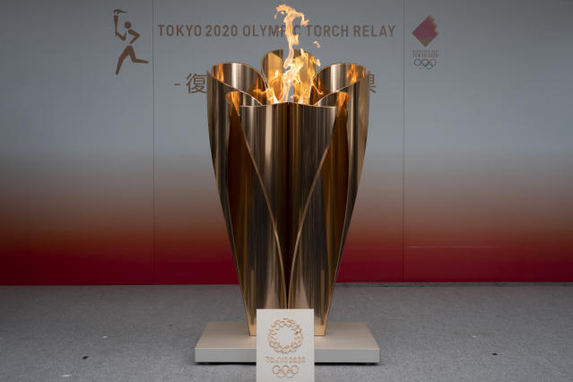 FILE - In this Tuesday, March 24, 2020, file photo, the Olympic flame is displayed during a public ceremony in Fukushima City, Japan. The Tokyo Olympics have been moved to next year. But countless questions remain. It's unclear how long the flame will stay there. It could remain for a year and be the focal point for games next year. Or it could move to Tokyo. (AP Photo/Jae C. Hong, File)