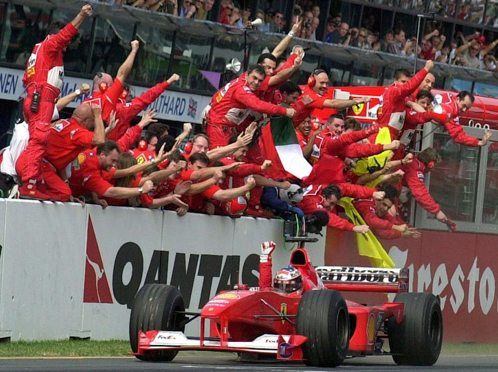 Michael Schumacher...FILE - In this March 12, 2000 file picture, Ferrari driver Michael Schumacher of Germany is cheered by his pit crew as he heads for the finish line to win the Australian Formula One Grand Prix in Melbourne. Seven-time Formula One champion Schumacher is making a comeback for Ferrari to replace injured driver Felipe Massa it was announced Wednesday July 29, 2009. Schumacher will get back in the cockpit until Massa is fit to return. The next race is the European Grand Prix on Aug. 23 in Valencia. (AP Photo/Rick Rycroft) - Credit: Rick Rycroft/AP