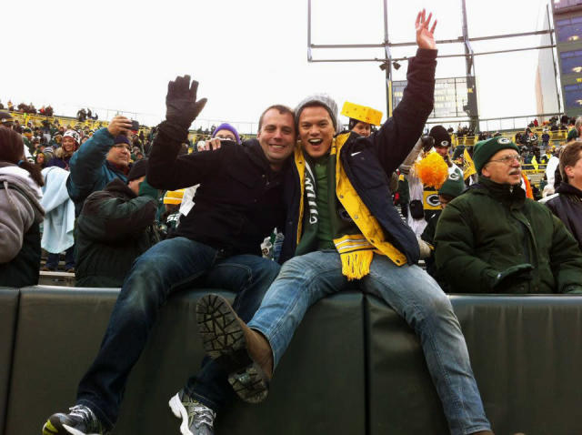 In this Nov. 20, 2011 photo provided by Paul Guequierre, James Servino, right and his boyfriend Paul Guequierre pose for a photo after the Green Bay Packers defeated the Tampa Bay Buccaneers in an NFL football game in Green Bay, Wis. When Michael Sam was drafted by the St. Louis Rams on May 10, 2014, he became the first openly gay player ever drafted by an NFL team. It is a milestone has made longtime gay fans all the more enthusiastic, and already is drawing newcomers into the fold. (AP Photo/Courtesy Paul Guequierre)