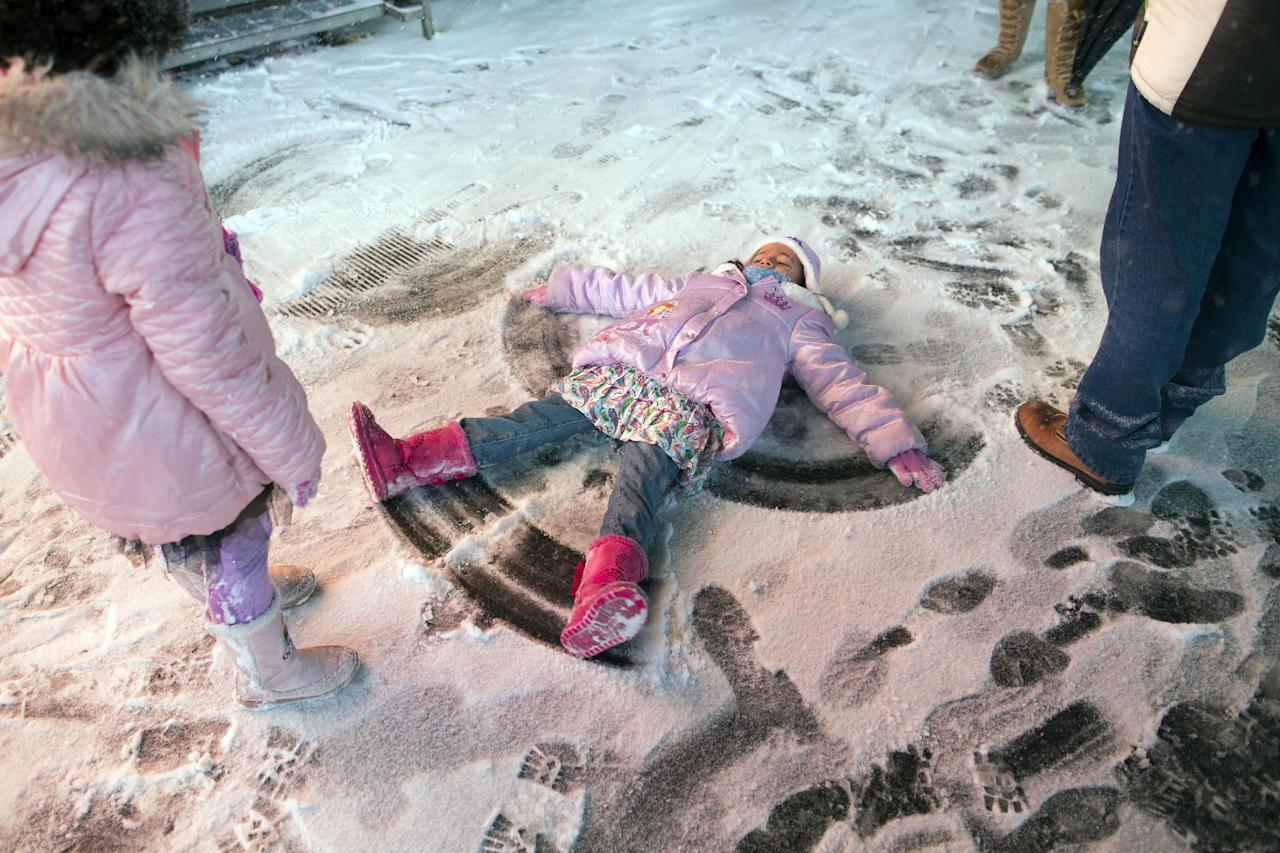 A child makes a snow angel in Times Square, Thursday, Jan. 2, 2014, in New York. The snow storm is expected to bring snow, stiff winds and punishing cold into the Northeast. (AP Photo/John Minchillo)