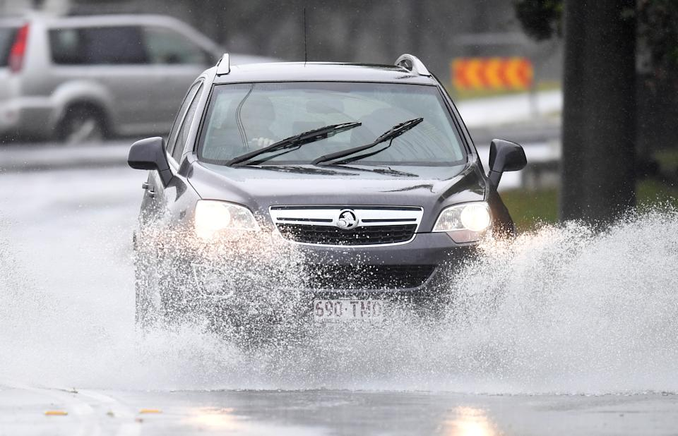 A car drives through a large puddle at Tweed Heads, NSW.