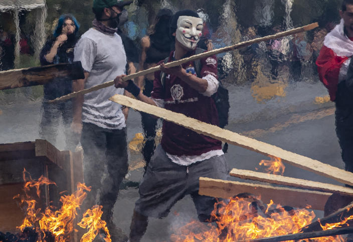 A demonstrator wearing a mask throws a plank of wood into a flaming barricade during a protests in Santiago, Chile, Saturday, Oct. 19, 2019. The protests started on Friday afternoon when high school students flooded subway stations, jumping turnstiles, dodging fares and vandalizing stations as part of protests against a fare hike, but by nightfall had extended throughout Santiago with students setting up barricades and fires at the entrances to subway stations, forcing President Sebastian Pinera to announce a state of emergency and deploy the armed forces into the streets. (Photo: Esteban Felix/AP)