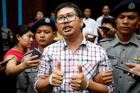 Detained Reuters journalist Wa Lone gestures as he is escorted by police after a court hearing in Yangon, Myanmar, August 20, 2018. REUTERS/Ann Wang/File Photo