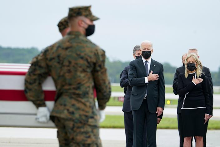 President Joe Biden and first lady Jill Biden watch a Marine Corps carry team move a transfer case containing the remains of Sgt. Johanny Rosario Pichardo, 25, of Lawrence, Mass., on Aug. 29, 2021, at Dover Air Force Base, Del.