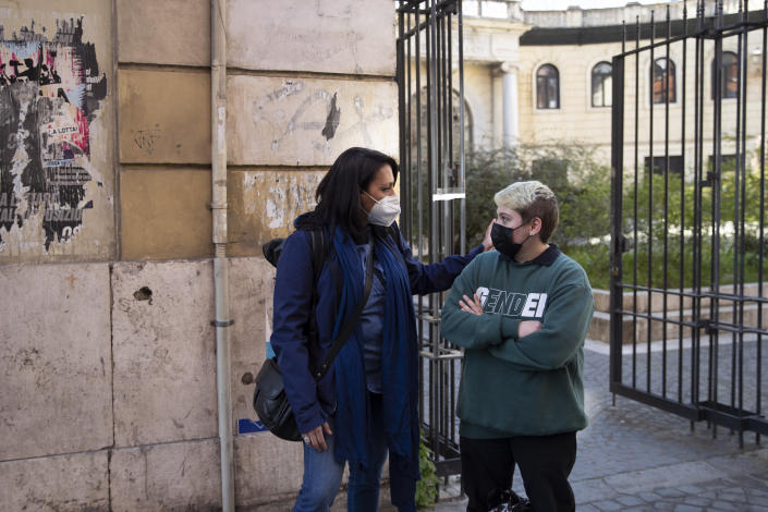 Matteo Coccimiglio talks with Sonia Mugello, a teacher at the Ripetta art Schools in Rome, Wednesday, March 24, 2021. Matteo is an 18-year-old student who identifies as a man and is in the process of changing his legal gender from female to male. The Ripetta school of art in Rome - where he studies - recently joined a handful of high schools in Italy that give transgender students the right to be known by a name other than the one they were given at birth. The initiative is meant to create an environment where transgender students feel secure and reflects a growing awareness in Italy of gender dysphoria among teenagers and children. (AP Photo/Alessandra Tarantino)