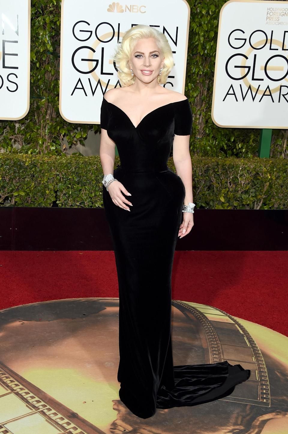 At the 2016 Golden Globe Awards, Lady Gaga chose a Versace dress and concealed her tattoos [Photo: Getty]