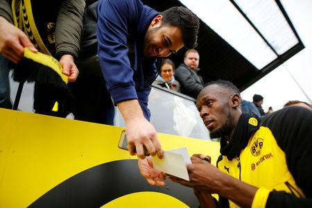 Soccer Football - Usain Bolt participates in a training session with Borussia Dortmund - Strobelallee Training Centre, Dortmund, Germany - March 23, 2018 Usain Bolt signs his autograph for fans after Borussia Dortmund training REUTERS/Thilo Schmuelgen