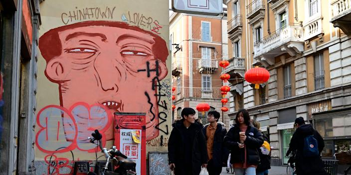 "People pass by a mural depicting a Chinese face in via Paolo Sarpi, the commercial street of the Chinese district of Milan on January 30, 2020. Several well-known figures in the Chinese community in Italy on January 30, 2020 denounced ""Discrimination without distinction"" and ""latent racism"" from Italians frightened by the coronavirus epidemic and the risks of contagion."