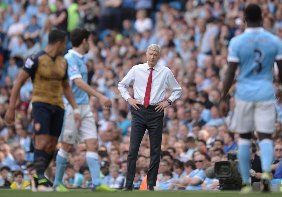 Arsenal manager Arsene Wenger (C) insists he will not consider extending his current deal until it is due to expire at the end of next season (AFP Photo/Oli Scarff )