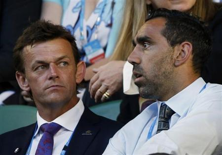 Australian cricketer Adam Gilchrist sits with Australian Football League (AFL) player Adam Goodes in the spectator stands ahead of the men's singles final match between Rafael Nadal of Spain and Stanislas Wawrinka of Switzerland at the Australian Open 2014 tennis tournament in Melbourne January 26, 2014. REUTERS/Jason Reed