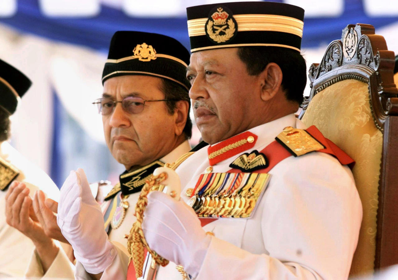FILE - In this June 1, 2002, file photo, then Malaysian King Syed Sirajuddin Syed Putra Jamalullail, right, and Malaysia's Prime Minister Mahathir Mohamad, left, pray during the Trouping the Colors in conjunction with Malaysia King's official birthday anniversary at the Independence Square in Kuala Lumpur, Malaysia. Sultan Muhammad V shocked the nation by announcing his abdication in January 2019, days after returning from two months of medical leave. The 49-year-old sultan from eastern Kelantan state only reigned for two years as Malaysia's 15th king and didn't give any reason for quitting. (AP Photo/TehEng Koon, File)