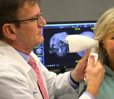 Otolaryngologist using Audioptics' Ossiview imaging system to view / examine patient's middle ear (CNW Group/Audioptics Medical)