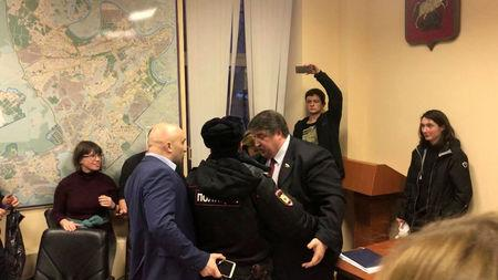 Policeman separates Dmitry Prokhorov, a local deputy of the pro-Kremlin United Russia party, and opposition deputy Vadim Korovin during session of a Moscow municipal council, in Moscow