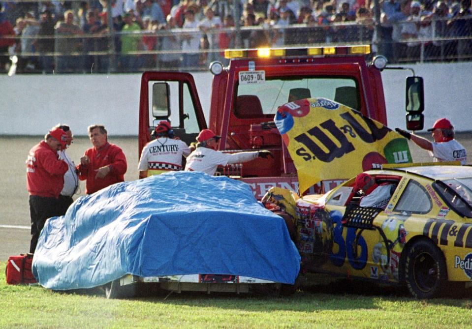 FILE - In this Feb. 18, 2001 file photo, safety workers cover Dale Earnhardt's (3) Chevrolet after crashing with Ken Schrader (36) during the Daytona 500 auto race at the Daytona International Speedway in Daytona Beach, Fla. Earnhardt, the greatest stock car star of his era, was killed in a crash on the last turn of the last lap of the race that day as he tried to protect Michael Waltrip's victory. (AP Photo/Greg Suvino, File