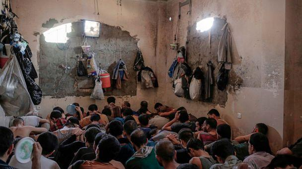 PHOTO: In this Tuesday, July 18, 2017 file photo, Suspected Islamic State members sit inside a small room in a prison south of Mosul, Iraq. (Bram Janssen/AP, File)