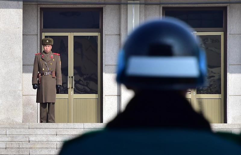 A North Korean soldier (L) and a South Korean soldier stand opposite each other at the truce village of Panmunjom in the Demilitarized Zone dividing the two Koreas on February 4, 2015 (AFP Photo/Jung Yeon-Je)
