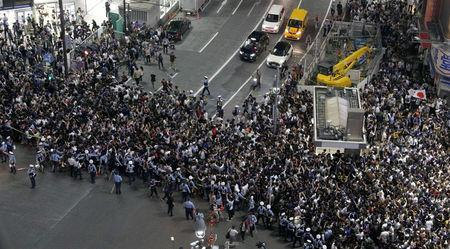 Police officers try to control Japanese soccer fans who gathered at an intersection after they celebrate the victory after the World Cup Group H soccer match Colombia vs Japan, at Shibuya district in Tokyo, Japan, in this photo take by Kyodo from the glass wall of 'MAGNET by Shibuya 109', June 19, 2018. Mandatory credit Kyodo/via REUTERS