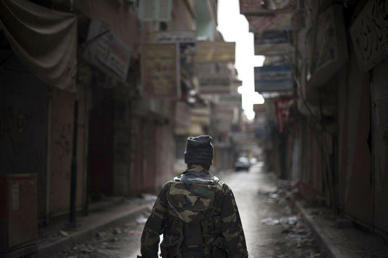 A rebel fighter walks through the Sit al-Ruba shopping street in the eastern city of Deir Ezzor, on February 16, 2013