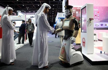 A visitor shakes hands with an operational robot policeman at the opening of the 4th Gulf Information Security Expo and Conference (GISEC) in Dubai, United Arab Emirates, May 22, 2017. Picture taken May 22, 2017. REUTERS/Stringer