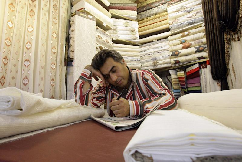 In this picture taken on Saturday, July 14, 2012, an Iranian textile merchant works on a crossword puzzle, as he waits for customer in Tehran's old main bazaar, Iran. While Iran's mainstay oil exports remains the centerpiece of Western sanctions _ intended to wring concessions on Iran's nuclear program and ease Israeli threats of a military strike _ the Islamic Republic hangs on as OPEC's third-largest exporter as it feeds the hungry energy markets in China, India and across Asia. But less noted _ but potentially more unsettling to Iran's leaders in the coming months _ is the increasing pinch on the workaday economy: The commerce, transactions and trading that provide the paychecks and economic lifelines for millions of people. (AP Photo/Vahid Salemi)