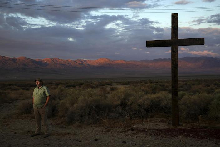 A man stands near a large cross against the backdrop of a desert valley rimmed by mountains