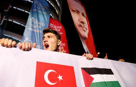 A demonstrator shouts slogans, as a portrait of Turkey's President Tayyip Erdogan is seen in the background, during a protest against the U.S. intention to move its embassy to Jerusalem and to recognise the city of Jerusalem as the capital of Israel, near the U.S. Embassy in Ankara, Turkey, December 6, 2017. REUTERS/Umit Bektas