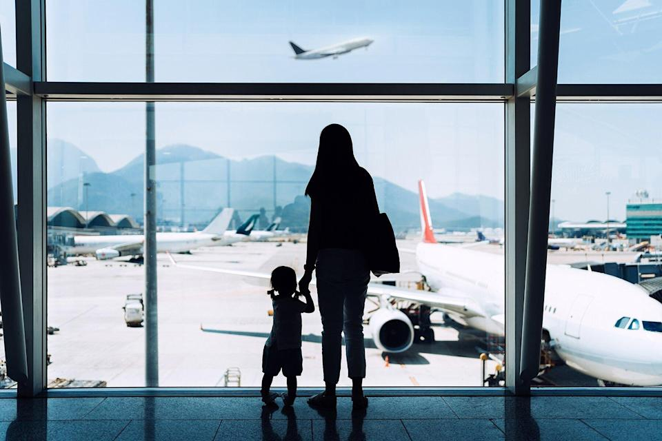 A mother holding hands daughter looking at airplane through window at the airport while waiting for departure