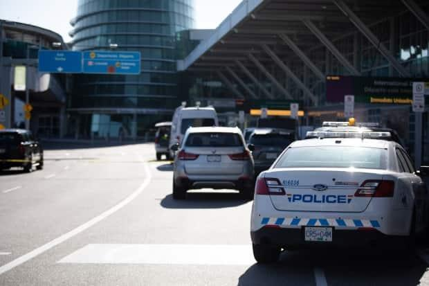 Police investigate a deadly shooting at Vancouver International Airport in Richmond, B.C., on Sunday. A man well known for having links to gang activity was killed outside the airport's departures terminal. (Maggie MacPherson/CBC - image credit)
