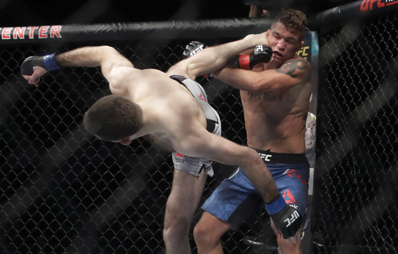 Ryan Hall, left, kicks Darren Elkins during a featherweight mixed martial arts fight at UFC Fight Night in Sacramento, Calif., Saturday, July 13, 2019. Hall won by unanimous decision. (AP Photo/Jeff Chiu)