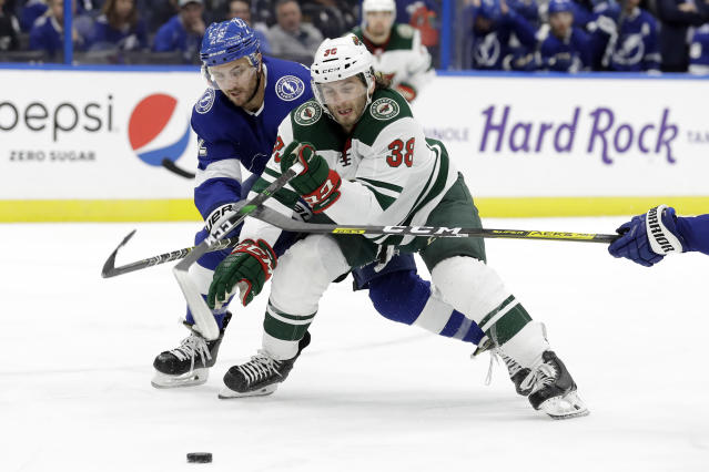 Minnesota Wild right wing Ryan Hartman (38) and Tampa Bay Lightning defenseman Kevin Shattenkirk (22) race for the puck during the third period of an NHL hockey game Thursday, Dec. 5, 2019, in Tampa, Fla. (AP Photo/Chris O'Meara)