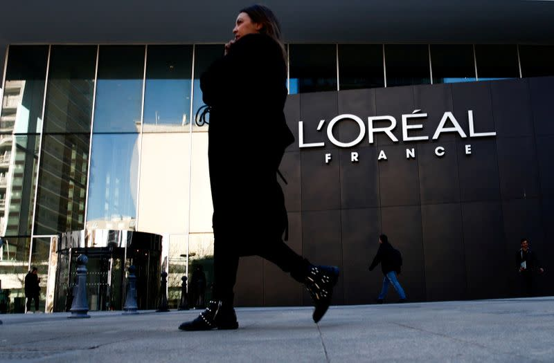 FILE PHOTO: A woman walks by the logo of French cosmetics group L'Oreal in the western Paris suburb of Levallois-Perret