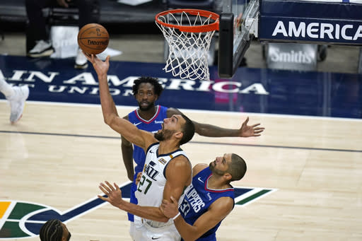 Utah Jazz center Rudy Gobert (27) scores against Los Angeles Clippers Nicolas Batum (33) during the second half of an NBA basketball game Friday, Jan. 1, 2021, in Salt Lake City. (AP Photo/Rick Bowmer)