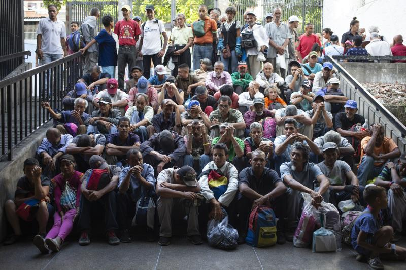 In this Feb. 27, 2020 photo, people wait outside of a religion center to receive a free meal in the slum called The Cemetery in Caracas, Venezuela.In the midst of a severe crisis, families in Venezuela struggle to consume enough food daily. A recent study by the UN World Food Program reveals that one in three residents of the South American country has difficulty bringing food to the table and fails to meet their basic nutritional requirements. (AP Photo/Ariana Cubillos)