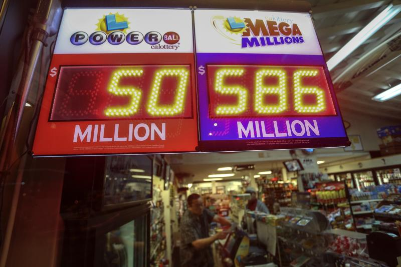 A worker at Nick's Liquor Store sells lottery tickets as a sign shows the Mega Millions jackpot estimated at $586 million in Venice, California December 16, 2013. The U.S. Mega Millions jackpot has grown to an estimated $586 million making it the second-largest drawing on record when the winning numbers are chosen on the night of Tuesday. REUTERS/Jonathan Alcorn (UNITED STATES - Tags: SOCIETY WEALTH)